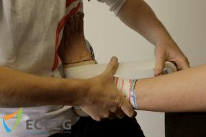 2. Het lichaam v/d therapeut houdt de voet in een dorsaalflexie. De tape wordt strak gezet om eversie te creëren. Middels de rechter duim kan de tape worden begeleid om plooivrij op de wreef te komen.
