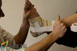 3. Met de linkerhand (kan ook met bijv. je lichaam) houd je de voet in de correcte positie (geen plantair, geen inversie), met rechts de tape over de gehele breedte vasthouden en strak houden (i.v.m. plooien)